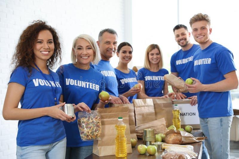 Drużyna wolontariuszi zbiera karmowe darowizny obrazy royalty free