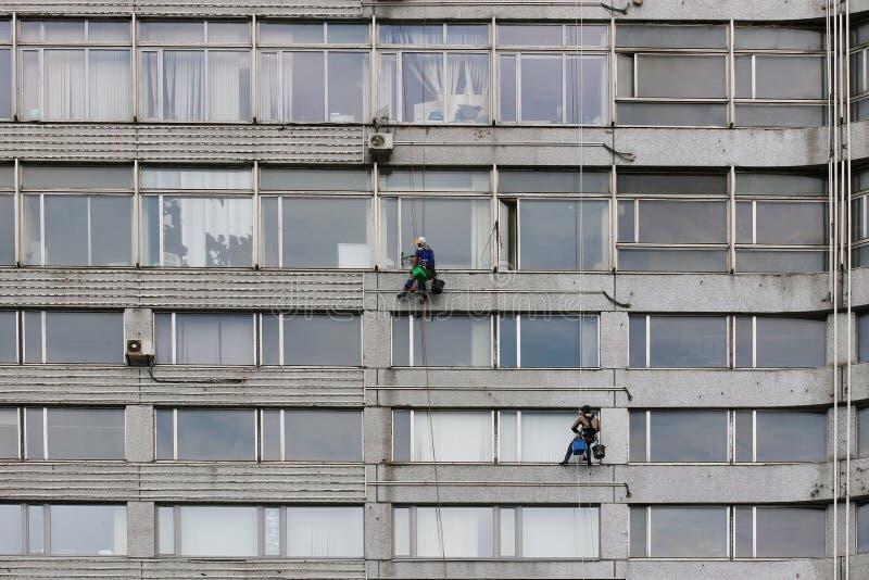 Drużyna wspinaczkowi pracownicy myje okno budynek w Moskwa fotografia stock
