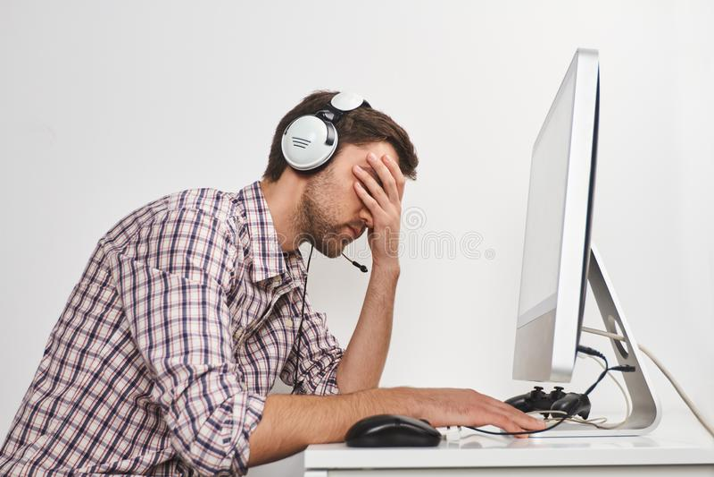 Drużynowa sztuka Cyber sport Portret młody nieszczęśliwy brodaty męski gamer w w kratkę koszulowym obsiadaniu przy stołem w świet obrazy stock