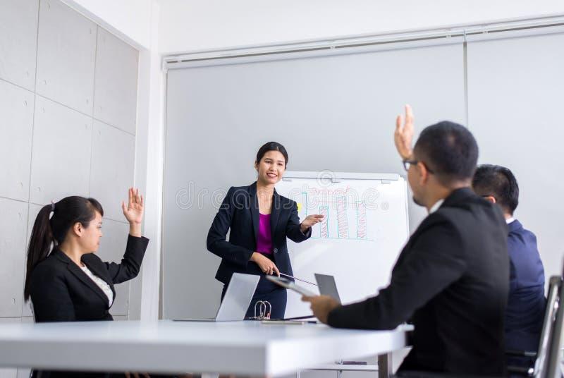 Drużynowego azjaty grupowy dyskutować z ręką podnosi w górę konferencji wpólnie wewnątrz przy biurem, pytanie i odpowied fotografia royalty free