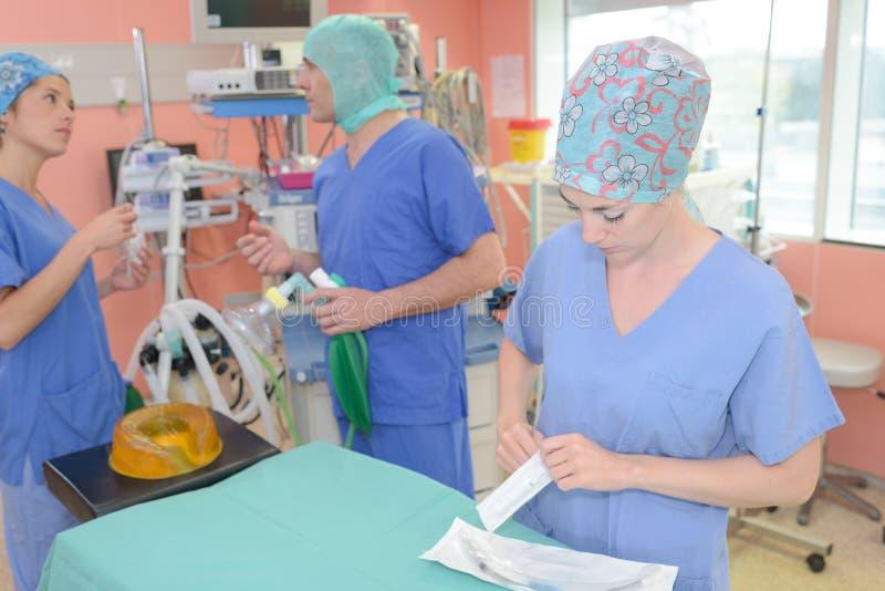 Drużynowi chirurdzy w ciemnej sala operacyjnej zdjęcia stock