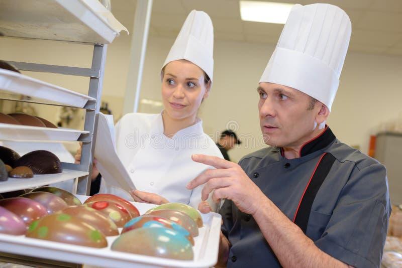 Drużynowi ciasto szefowie kuchni pracuje przy ciastem zdjęcia stock