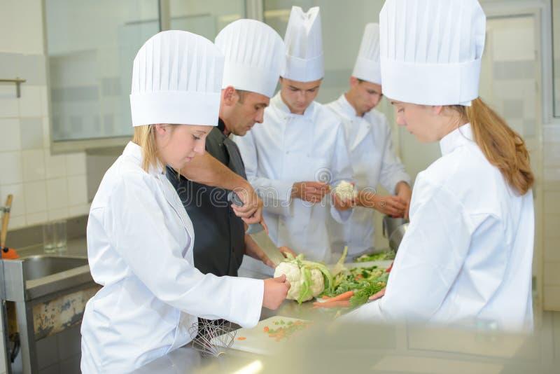 Drużynowi praktykantów szefowie kuchni przygotowywa warzywa obraz royalty free