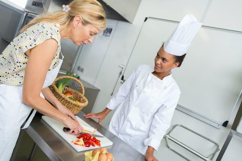 Drużynowi szefowie kuchni sieka warzywa na ciapanie desce w kuchni obraz royalty free