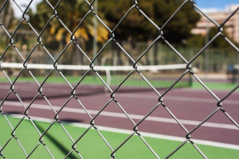 Druciany ogrodzenie przy pustym tenisowym sądem zdjęcia royalty free