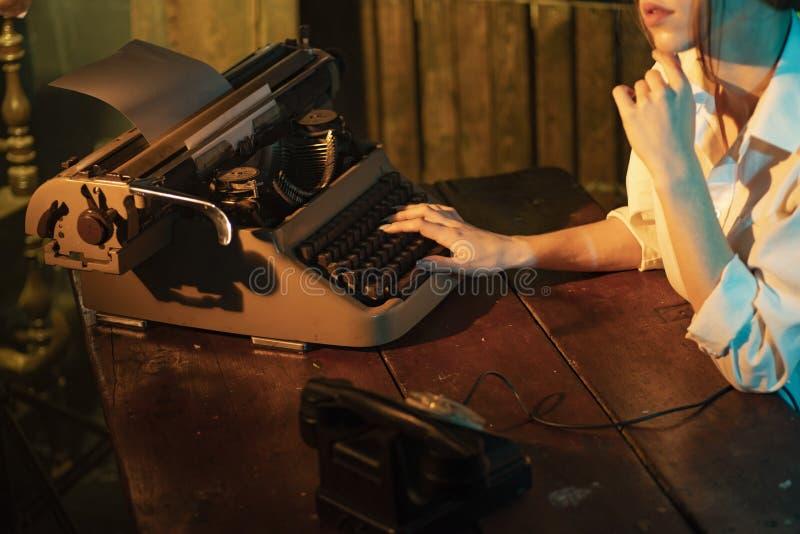 Druck auf Schreibmaschinenmädchen Ein Mädchen schreibt einen Buchstaben auf einer alten Schreibmaschine lizenzfreie stockbilder