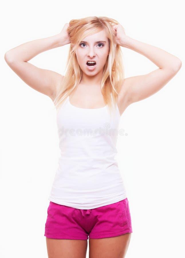 Druck. Junge Frau frustriert, ihr Haar auf Weiß ziehend lizenzfreies stockbild