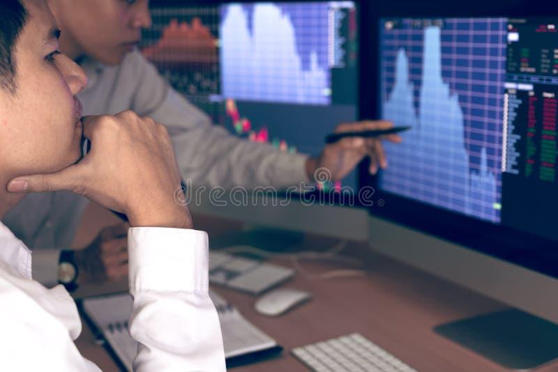 Druck mit zwei Geschäftsbörsenmaklern und Betrachten von den Monitoren, die Finanzinformationen anzeigen stockbilder