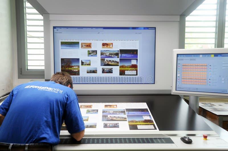 Drucker, der bei Tisch eine Auflagenstärke überprüft lizenzfreie stockbilder