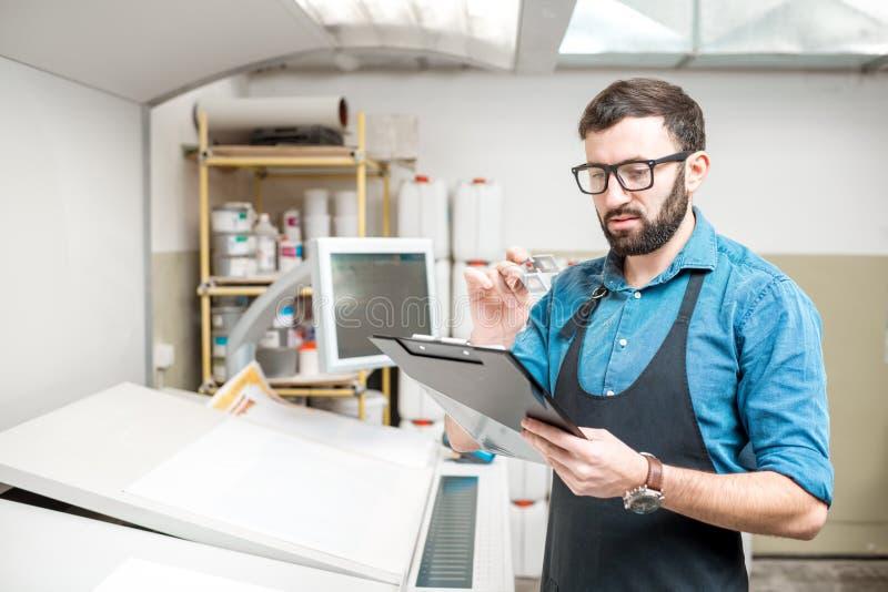 Drucker, der in dem Druckbetrieb arbeitet stockfoto