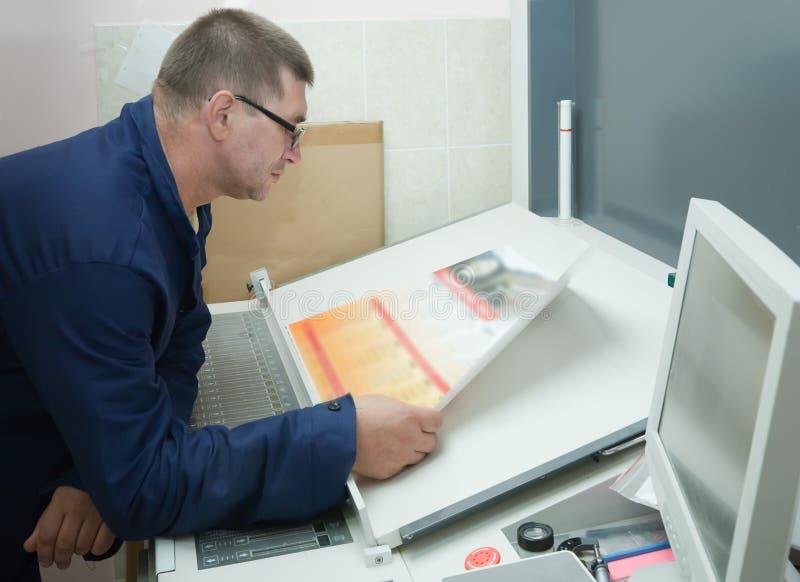 Drucker, der eine Auflagenstärke überprüft lizenzfreies stockbild