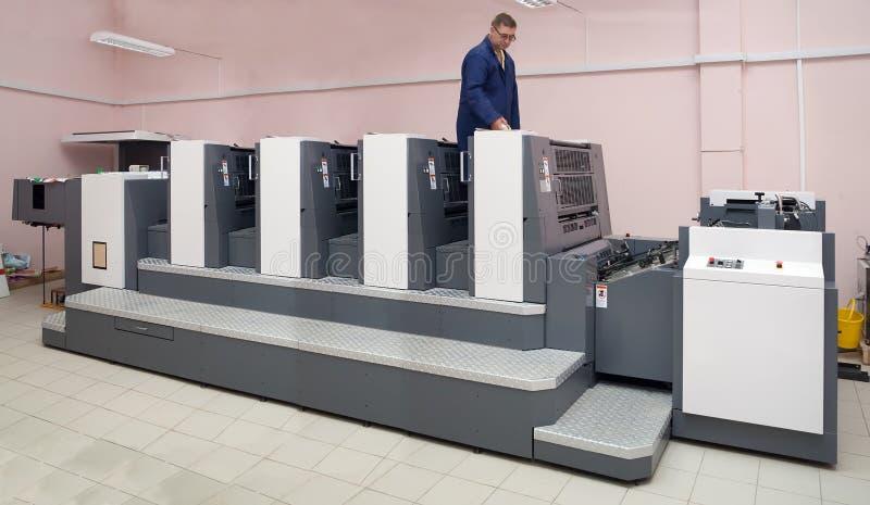Drucker, der Vierkapitel an der Offsetmaschine arbeitet stockfotografie