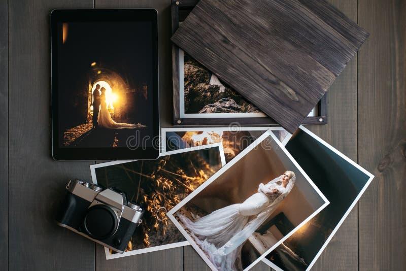 Druckheiratsfotos, Holzkiste, eine Weinleseschwarzkamera und eine schwarze Tablette mit einem Bild eines Hochzeitspaares lizenzfreies stockfoto
