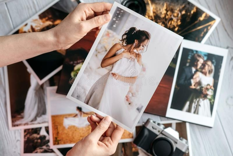 Druckheiratsfotos mit der Braut und dem Bräutigam, eine Weinleseschwarzkamera und Frauenhände mit Foto stockfoto