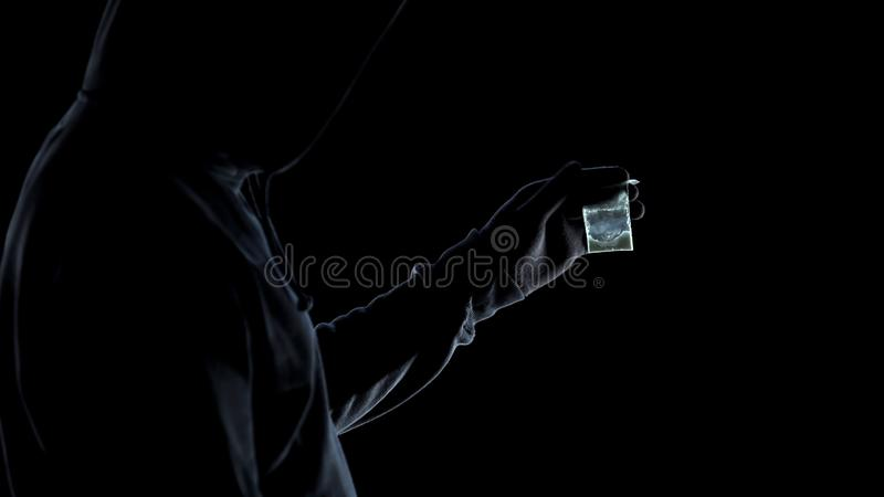 Drug addict male in hoodie looking at packet with amphetamine, addiction issue royalty free stock images
