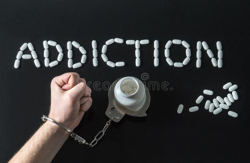 Drug addict or medical abuse. Concept with man handcuffed to a medicine bottle. Obsession to pharmaceutical substances or narcotics or anxiety pills. Addiction stock images