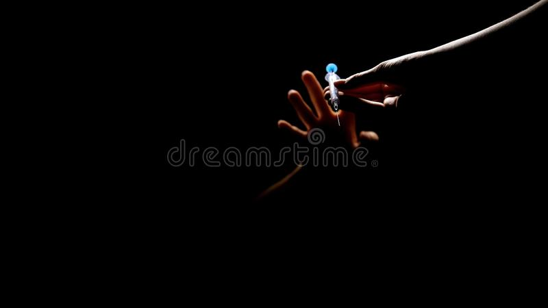 Drug addicted person taking syringe with dose from dealer hands in darkness royalty free stock photos