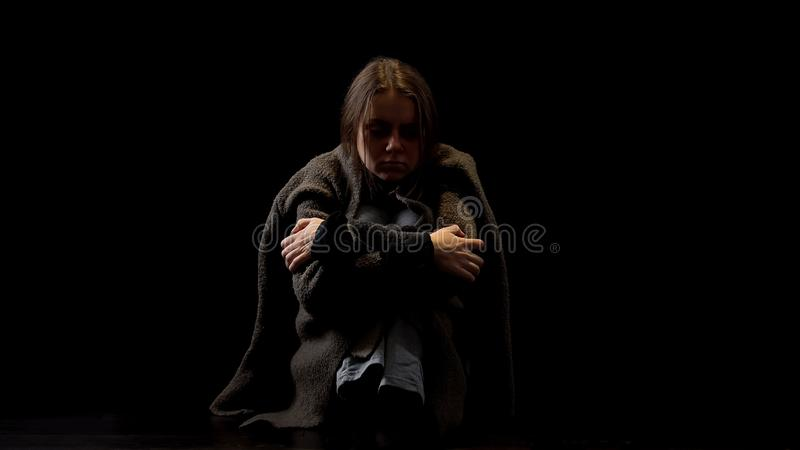 Drug addicted woman sitting alone in darkness, miserable victim of violence. Stock photo stock photo