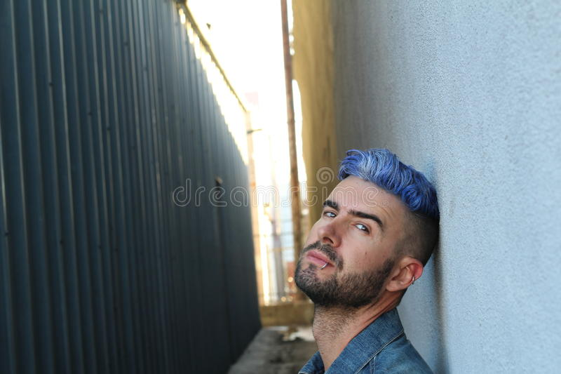 Drug addicted young rebel man with blue dyed hair sitting on suspicious dark alley way stock images