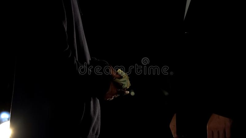 Drug dealer counting money selling dose to client, counterfeit money, ambush royalty free stock photo