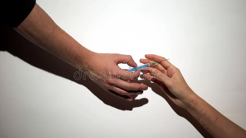 Drug dealer hand giving self-inflicted addict syringe with dose, mental disease. Stock photo stock images