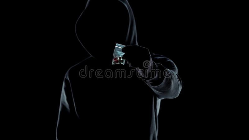 Drug dealer in hoodie showing packet with LSD pills at camera, addiction problem stock photos