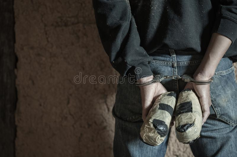 Drug dealer under arrest confined with handcuffs and hands at his back, standing next to a wall.  stock photo