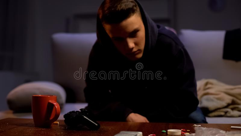 Drug intoxicated teen sitting on sofa after night party, narcotic addiction. Stock photo royalty free stock photo