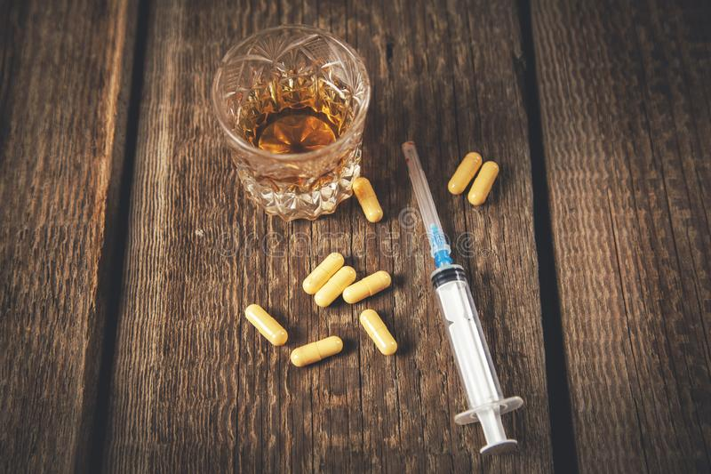Drug met spuit en whisky stock afbeelding