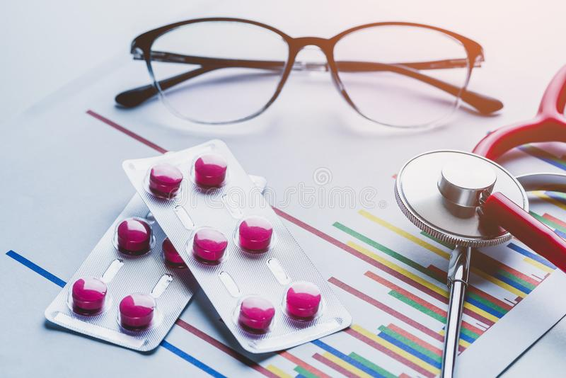 Drug, pills and glasses with stethoscope on lab table. And Drug test report graph stock photography