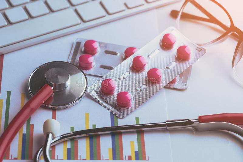Drug, pills and glasses with stethoscope on lab table. And Drug test report graph royalty free stock photos