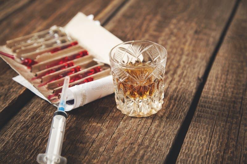 Drug with syringe and whiskey. On the desk stock photo