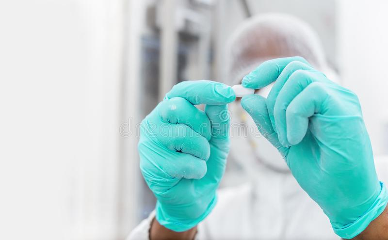 Drug tablet being inspected for quality. stock photo