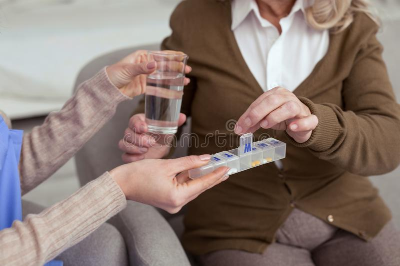 Young nurse proposing pills for elder woman royalty free stock image