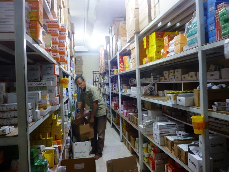 Drug warehouse. Worker putting boxes together on shelves in modern drug warehouse stock photos
