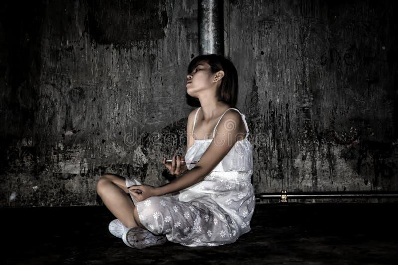 Druggebruik concept , het gebruikssyrin van de overdosis Aziatische vrouwelijke drugverslaafde stock afbeelding