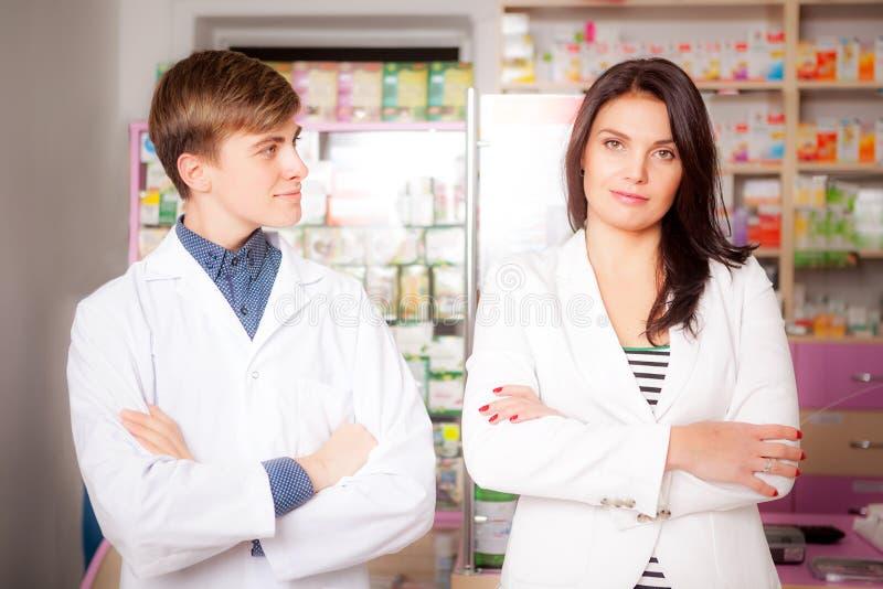 Druggist и клиент перед таблицей фармации стоковое фото