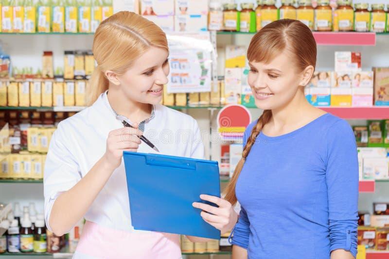 Druggist и клиент с доской сзажимом для бумаги стоковые изображения