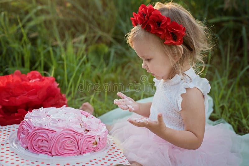 Drugi urodziny ma?a dziewczynka Dwa lat dziewczyna siedzi blisko świętowanie dekoracji i je jej urodzinowego tort Tortowy roztrza obrazy royalty free