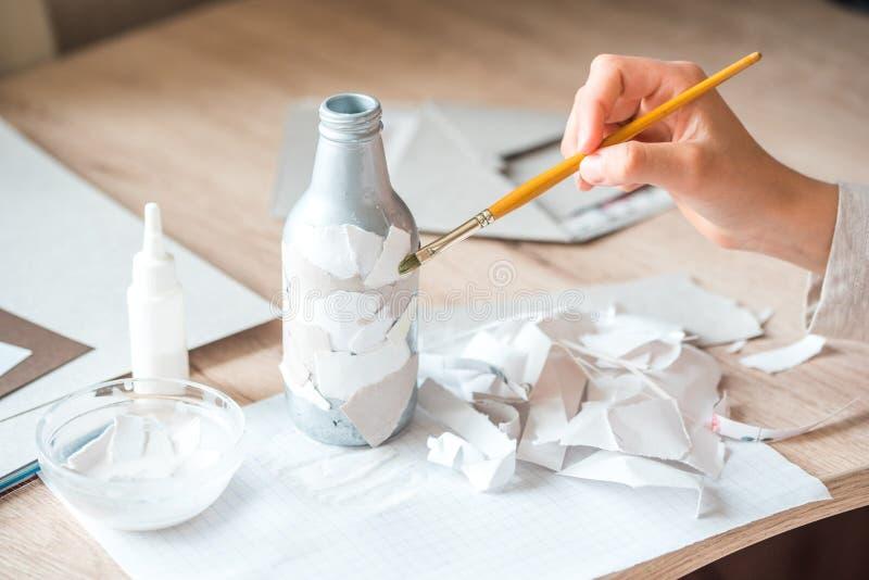 drugorzędny use papierowi gruzy children handmade od papier - mache Dziecko ręki kleią kawałki papieru na bottl obrazy stock