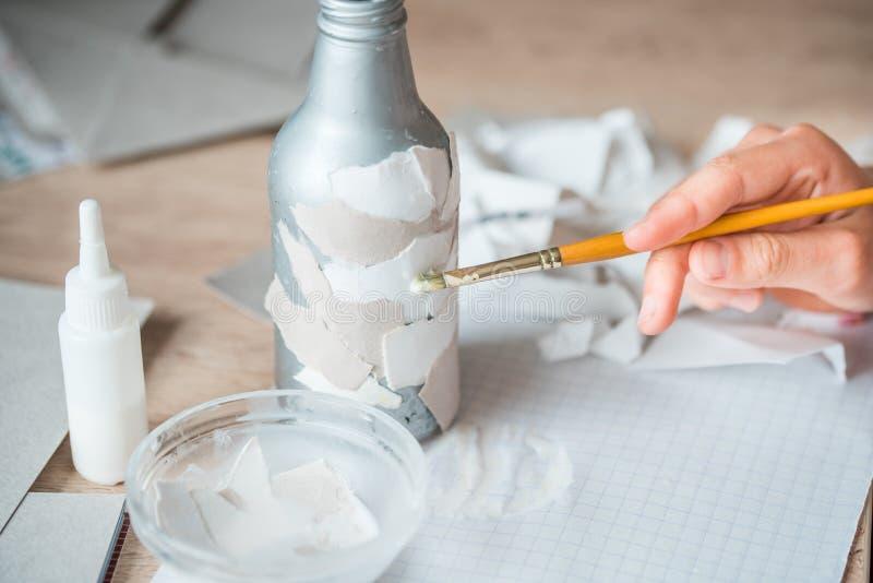 drugorzędny use papierowi gruzy children handmade od papier - mache Dziecko ręki kleią kawałki papieru na bottl zdjęcie stock