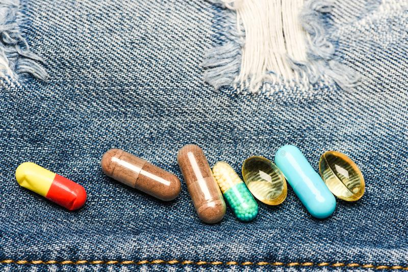 Drugs on denim background. Set of colorful pills. Mixing medicines. Fast treatment. Medicine prescription. Health care royalty free stock photos