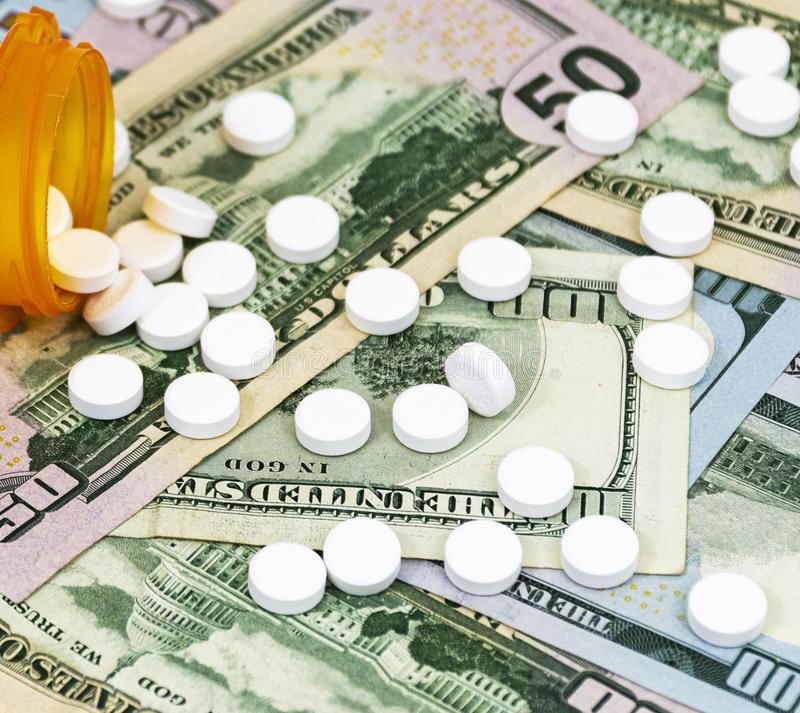 Drugs spill out on to us cash one firfty and one hundred dollar bills royalty free stock images