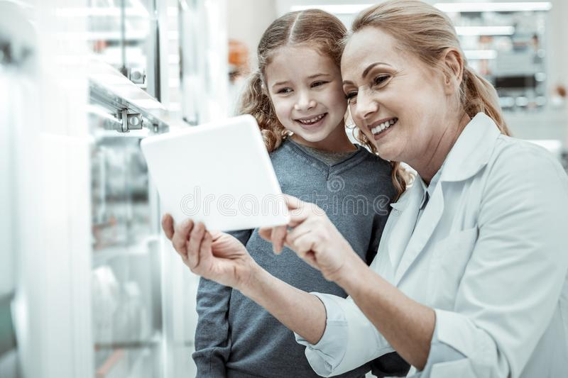 Drugstore worker considering vitamins assortment via tablet with a girl. Considering assortment. The female smiling drugstore worker considering a vitamins royalty free stock image