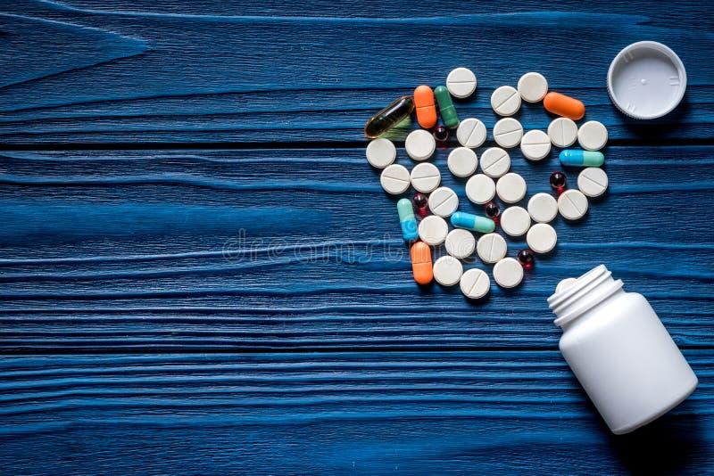 Drugtherapie Pillen en pillenfles op blauwe houten lijst hoogste mening als achtergrond copyspace royalty-vrije stock afbeeldingen