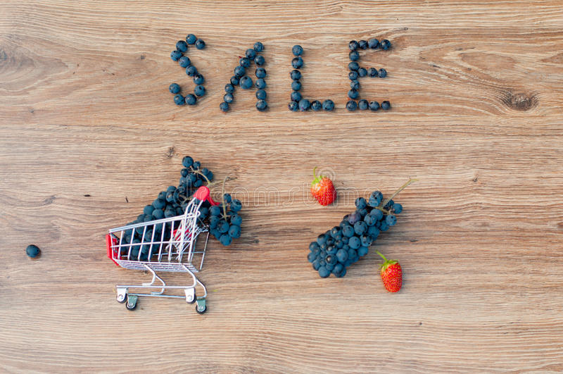 Druiven binnen klein boodschappenwagentje, woordverkoop en percententeken stock afbeeldingen