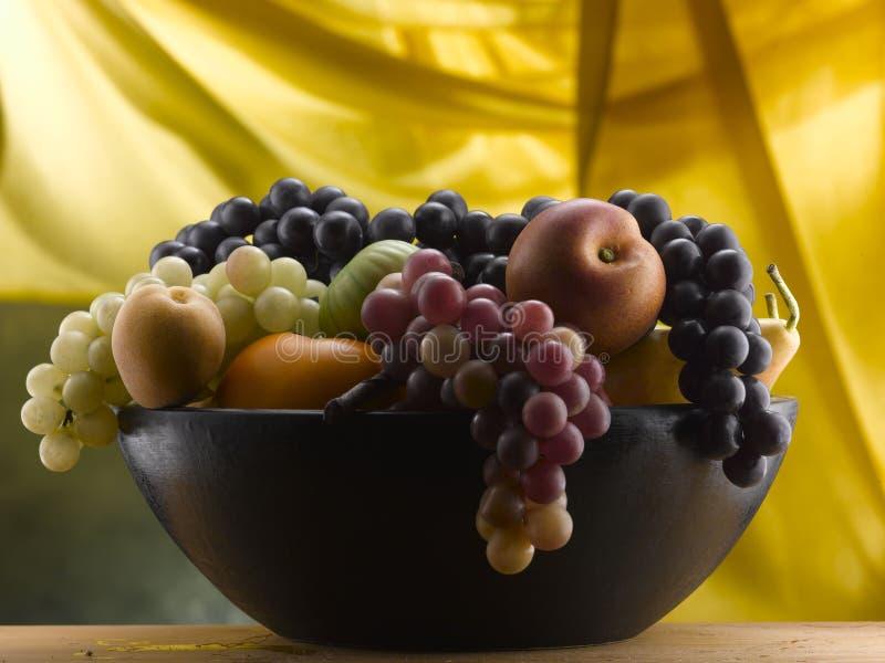 Druiven en ander fruit in een houten kom royalty-vrije stock afbeelding