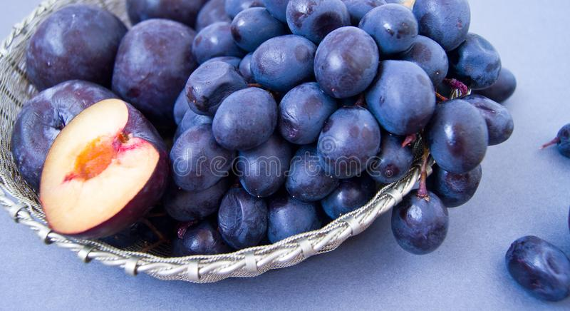 Druiven en pruimen in een zilveren kom stock afbeeldingen