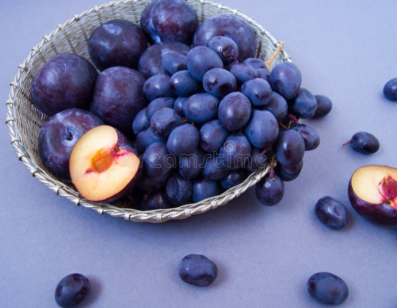 Druiven en pruimen in een zilveren kom stock foto
