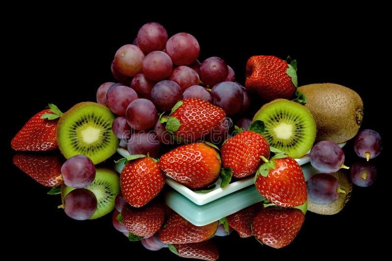Druiven, kiwi en aardbeien op een zwarte achtergrond stock afbeeldingen